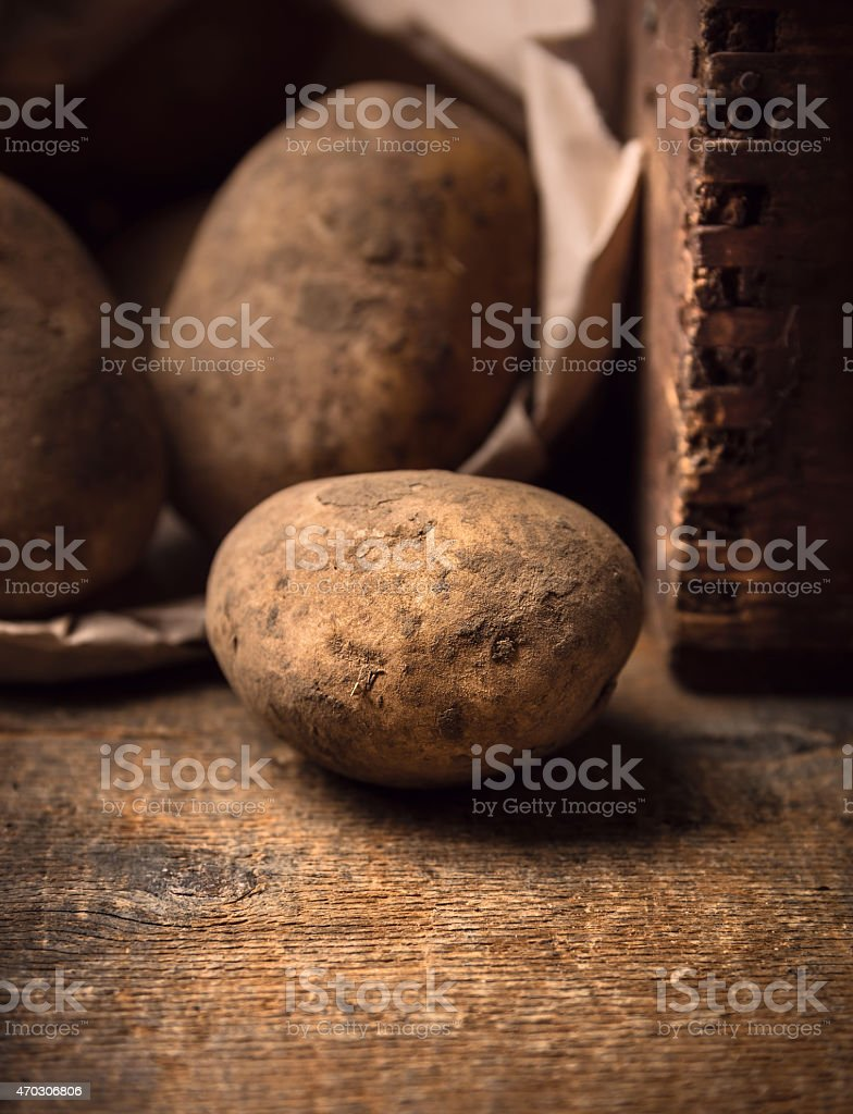 raw organic potatoes on dark wooden rustic background stock photo