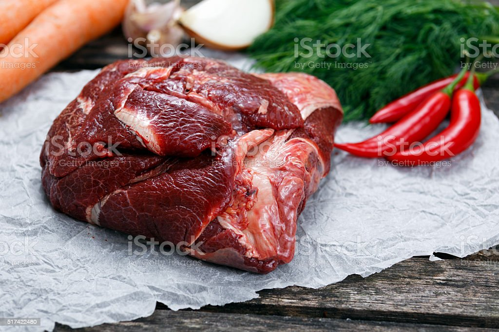Raw Ox Cheek on crumpled paper,  decorated with vegetables. stock photo