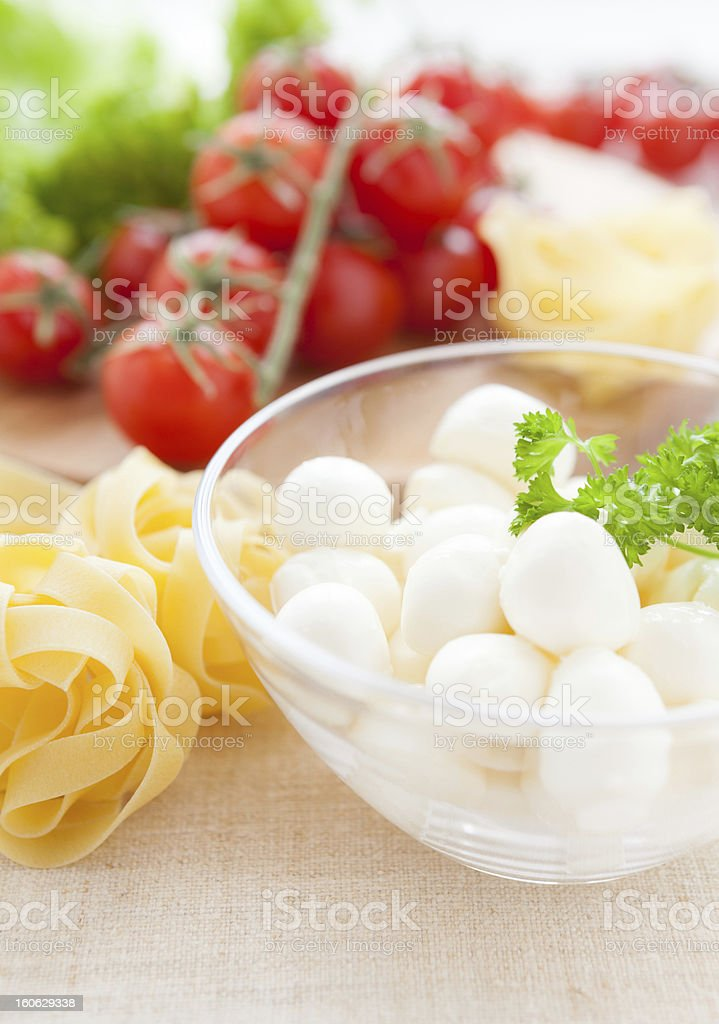 raw pasta in a bowl and mozzarella, cherry tomatoes royalty-free stock photo