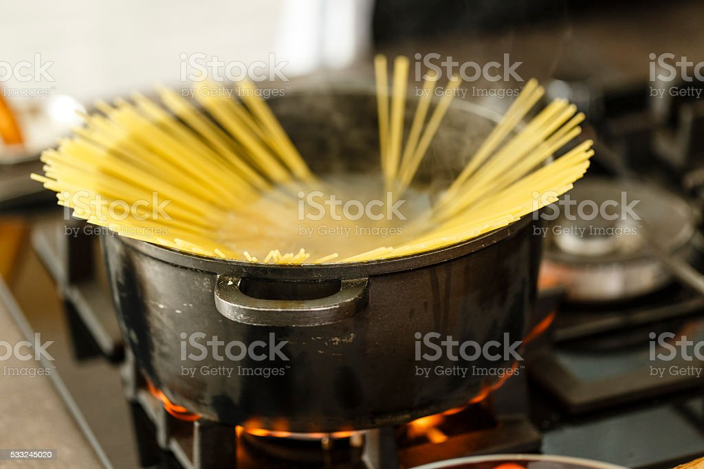 Raw pasta in saucepan on stove stock photo