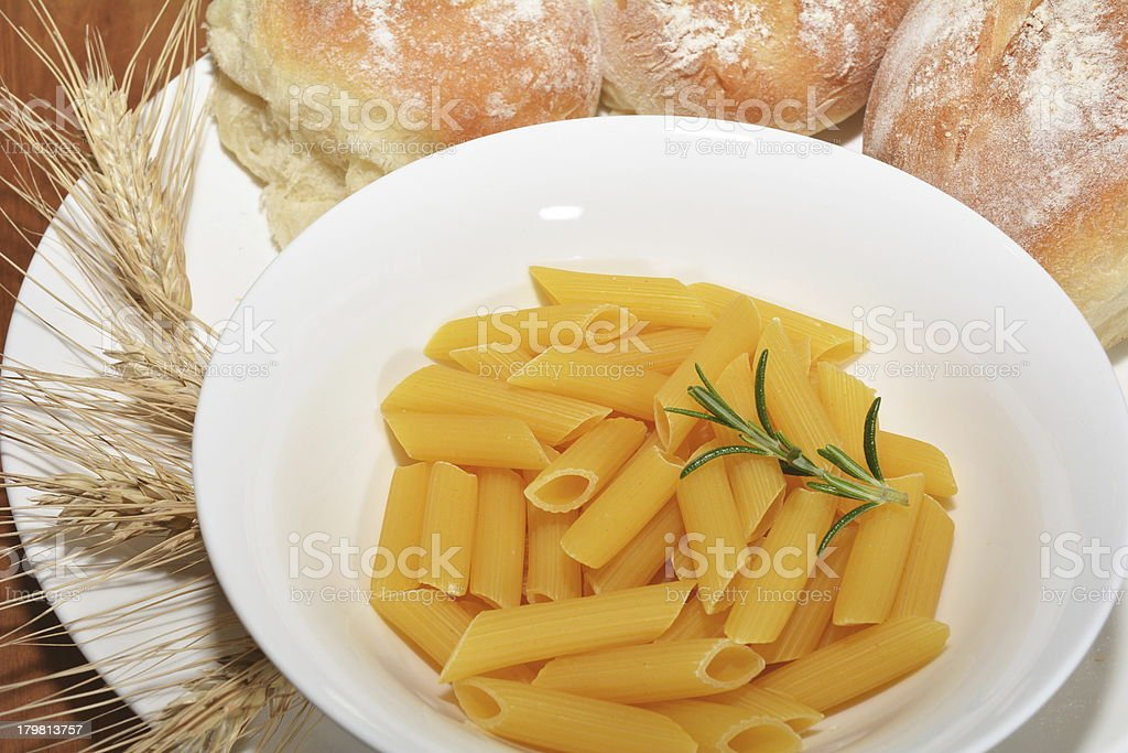 Raw pasta with bread rolls and wheat husks royalty-free stock photo