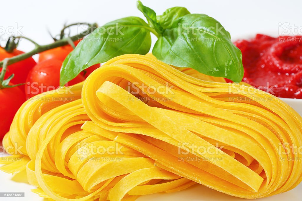 Raw pasta with tomatoes stock photo