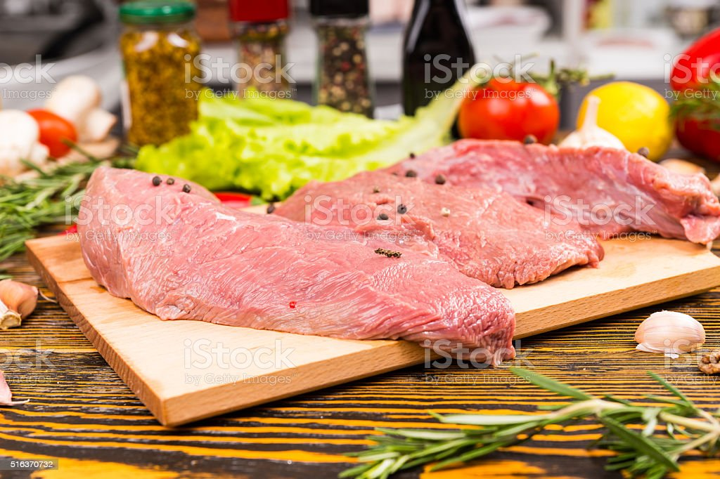 Raw pieces of meat with peppers on top stock photo