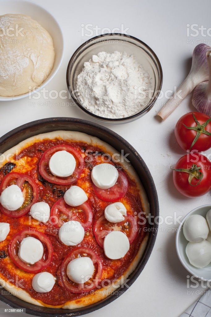Raw pizza margarita with ingredients close-up on a white table. View from above stock photo