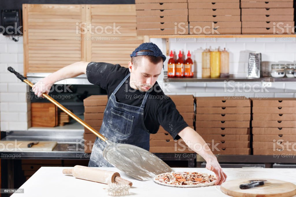 Raw pizza ready to bake. Cook in a blue apron in the kitchen. with a shovel in his hands. boxes for food delivery on background. stock photo