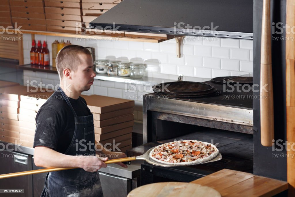 Raw pizza ready to Bake in the oven. Cook in a blue apron in the kitchen. with a shovel in his hands. stock photo