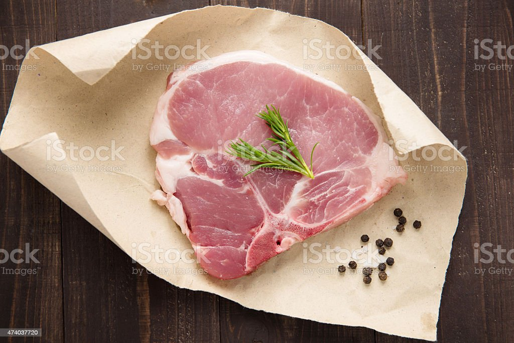 raw pork chop steak on paper and wooden background stock photo