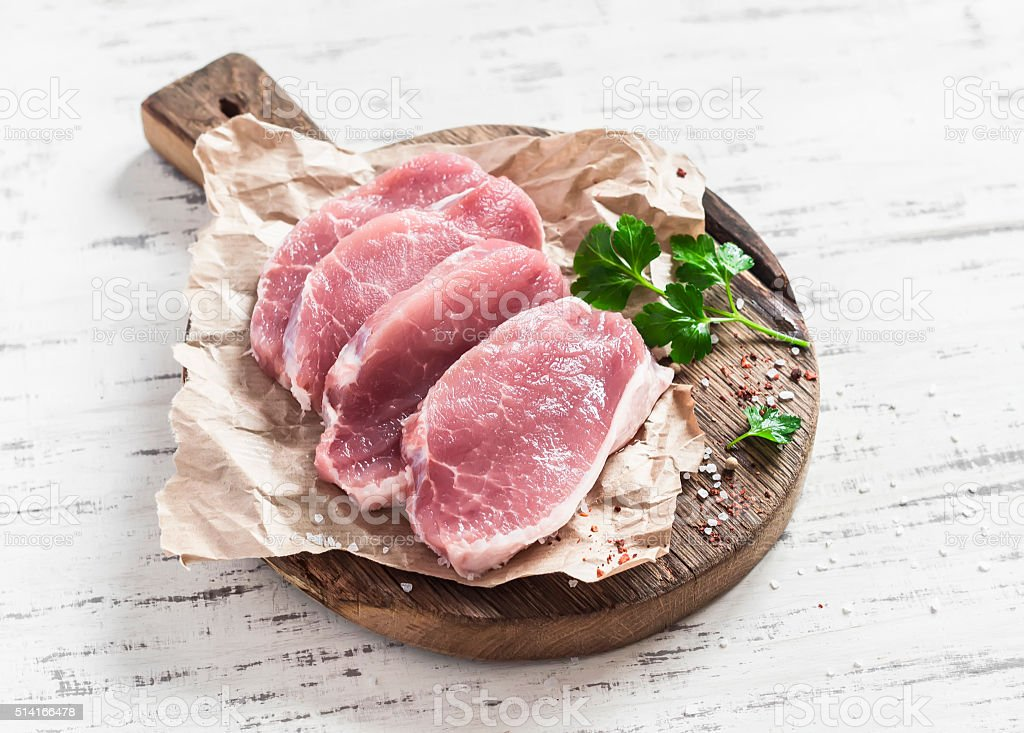 Raw pork chops  on a rustic wooden cutting board stock photo