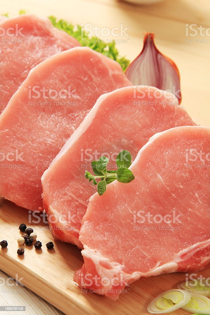 Raw pork chops on a wooden board royalty-free stock photo