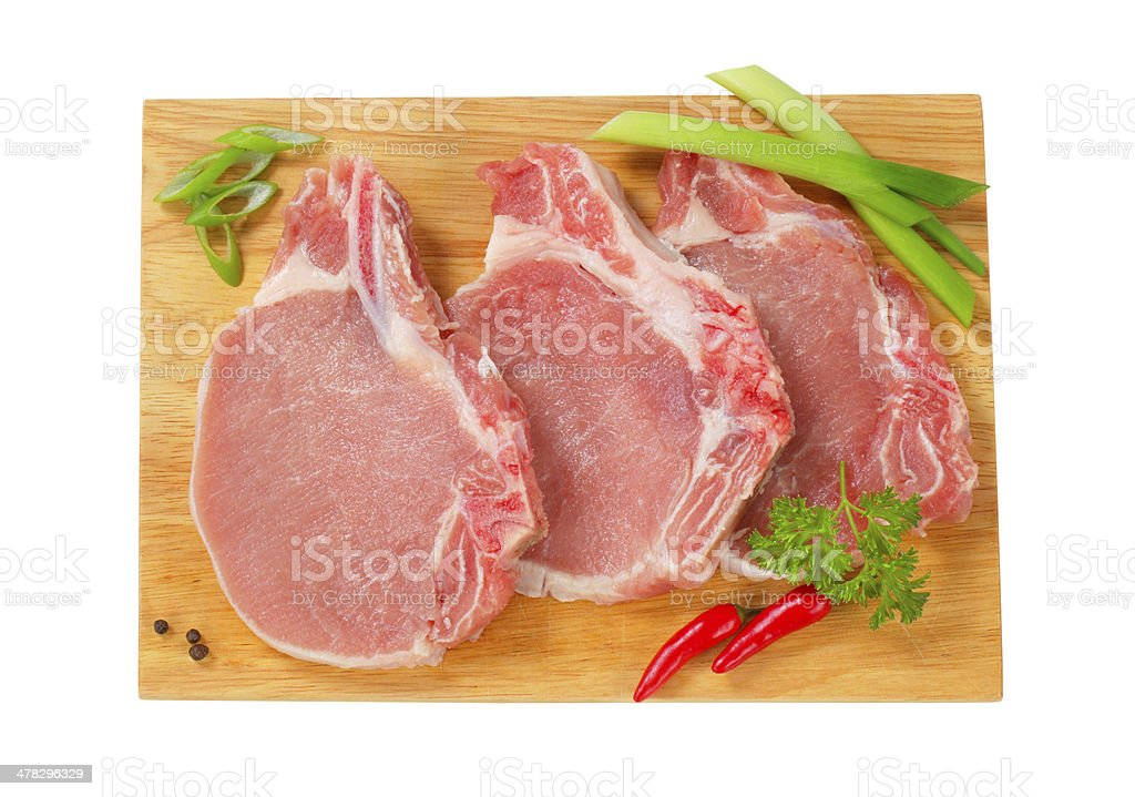 raw pork chops with herbs on a cutting board royalty-free stock photo