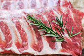 Raw Pork ribs with a rosemary. on crumpled paper