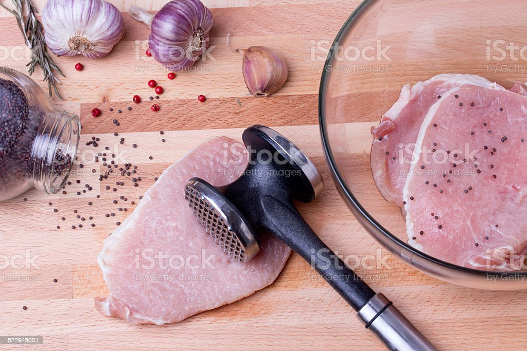 Raw pork schnitzel with meat tenderizer on wooden board stock photo