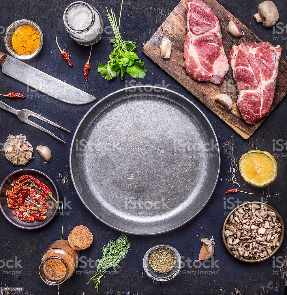 raw pork steak herbs, mushrooms garlic around pan  top view stock photo