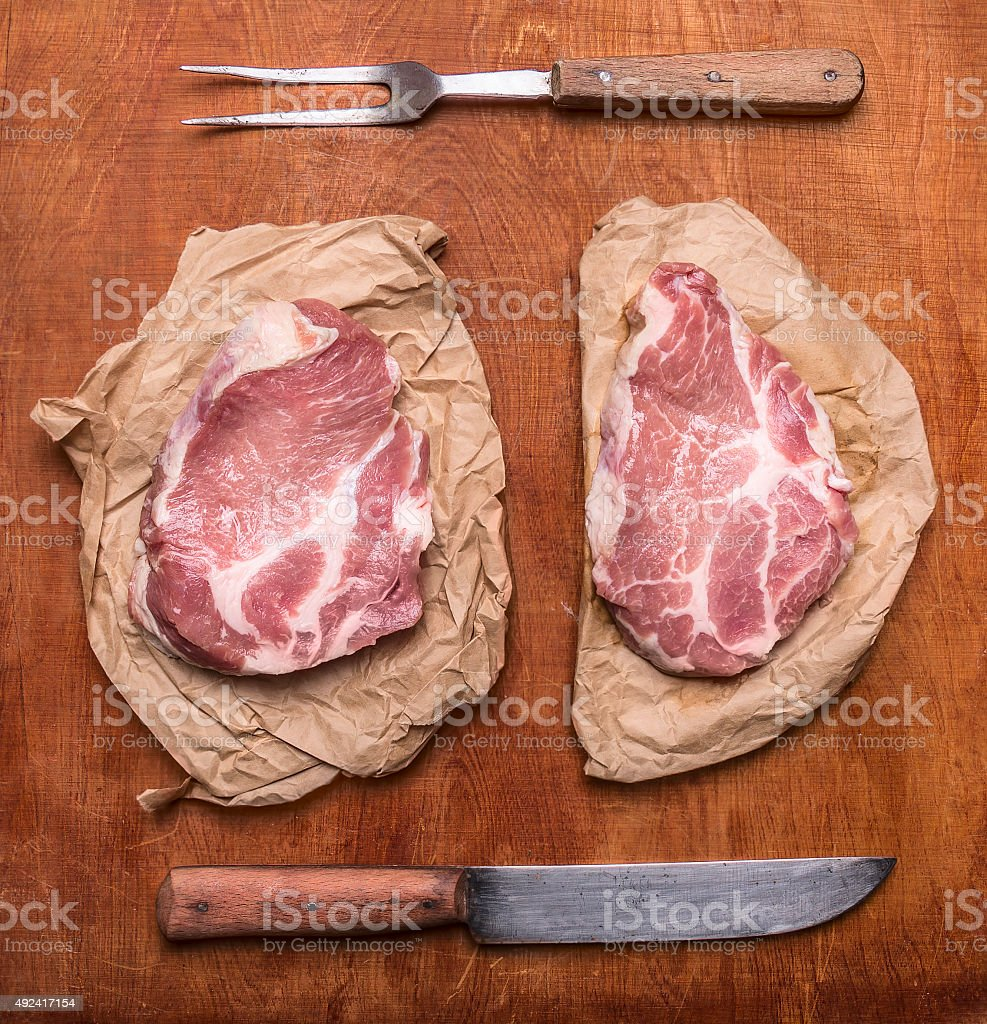 raw pork steak knife  rustic wooden background view close up stock photo