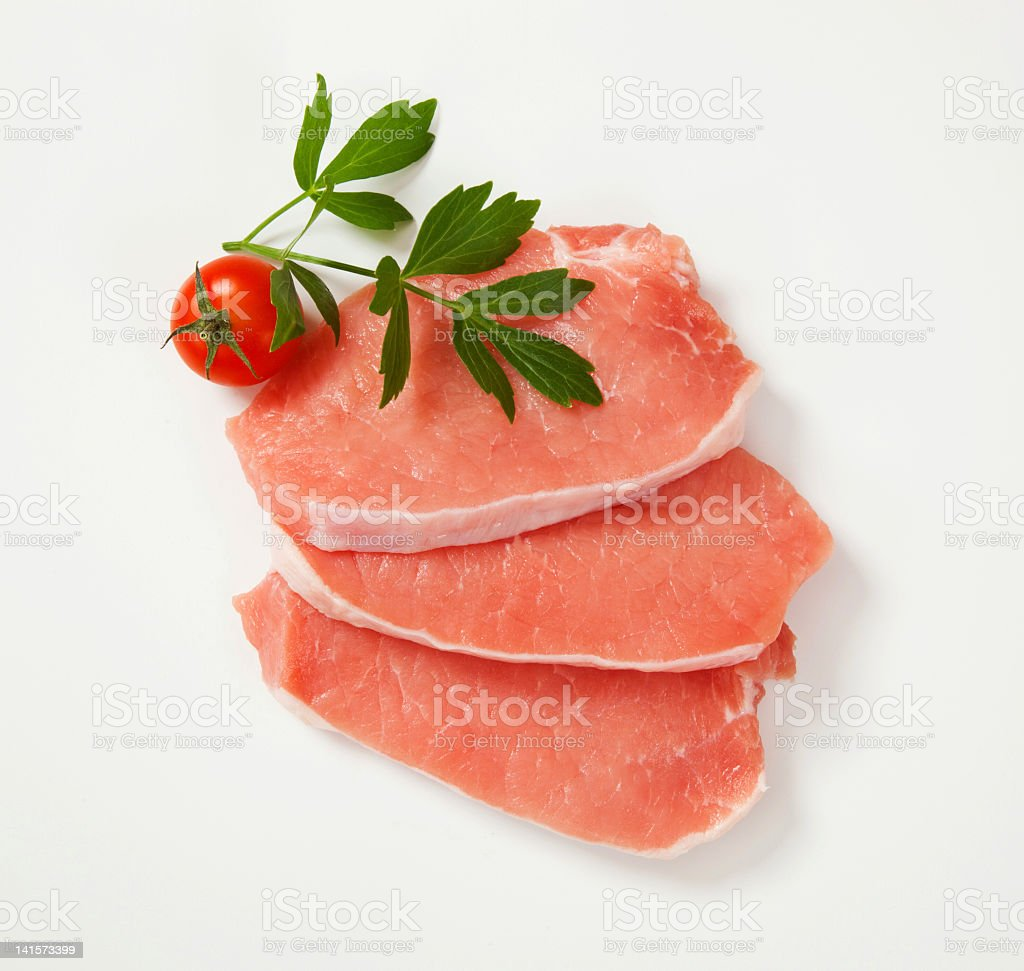 Raw pork steaks (three), lovage, cherry tomato, white background stock photo