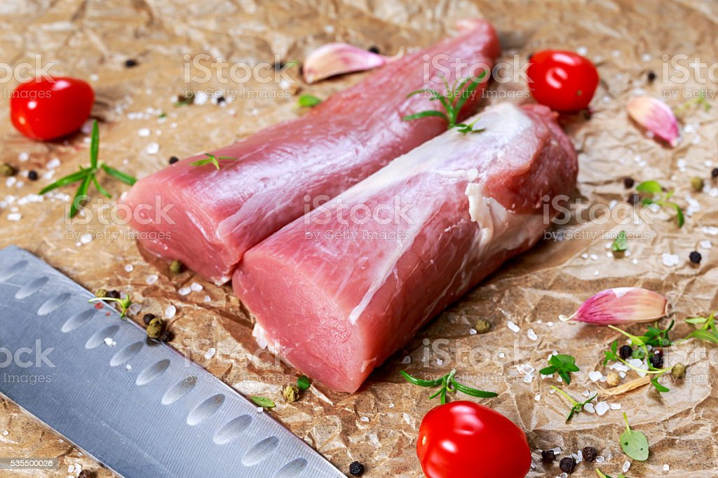 Raw pork tenderloin on crumpled paper. ready to cook. stock photo