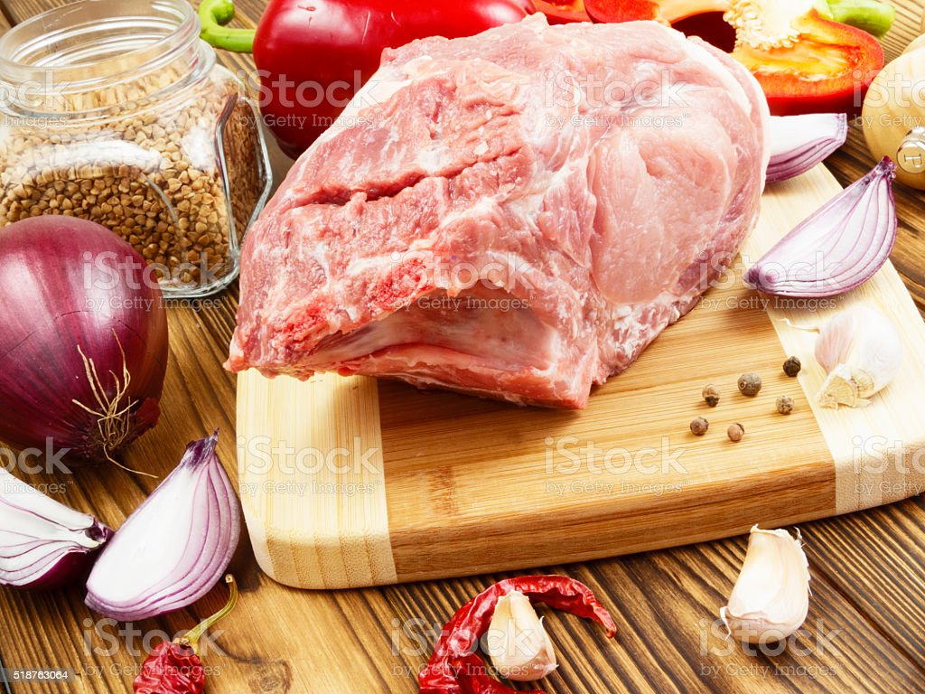 raw pork with vegetables and spices stock photo