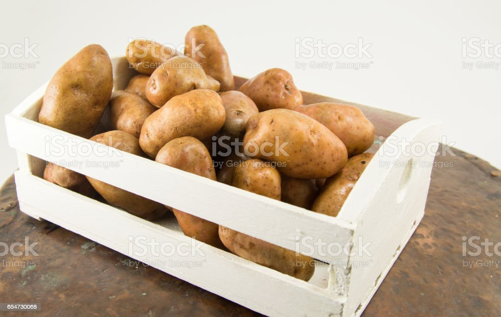 raw potatoes in a basket stock photo