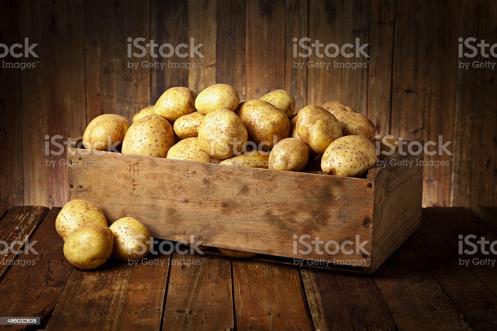 Raw potatoes in a crate on rustic wood table stock photo