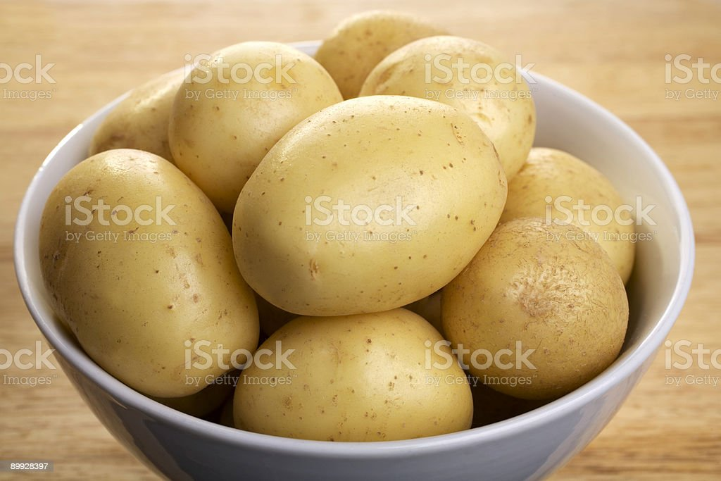 Raw Potatoes in a White Bowl stock photo