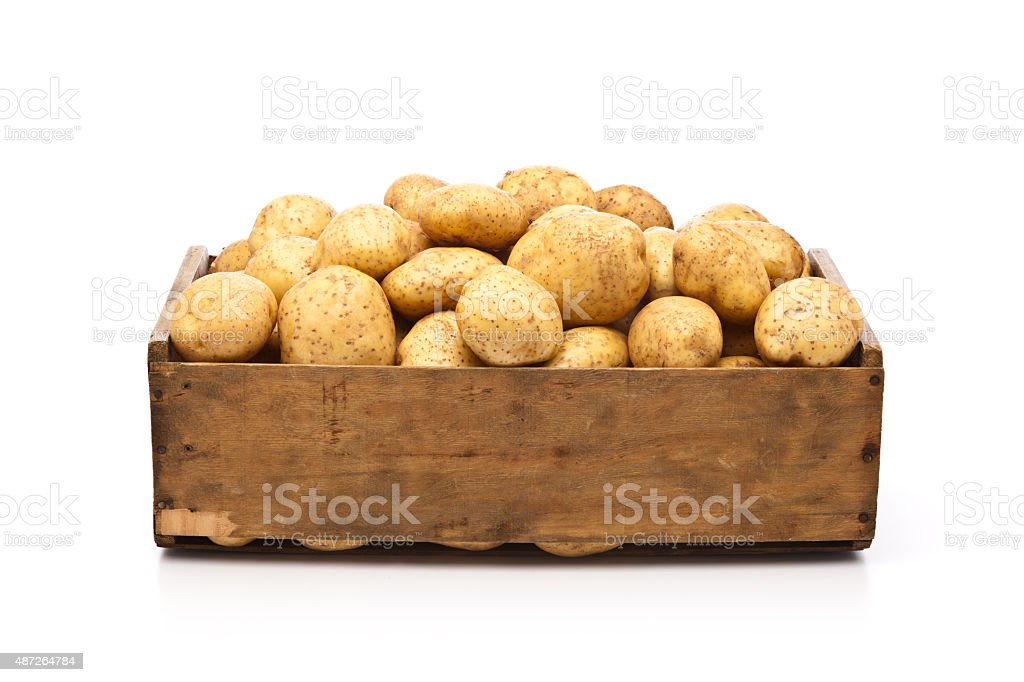 Raw potatoes in a wooden crate isolated on white backdrop stock photo