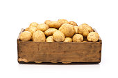 Raw potatoes in a wooden crate isolated on white backdrop