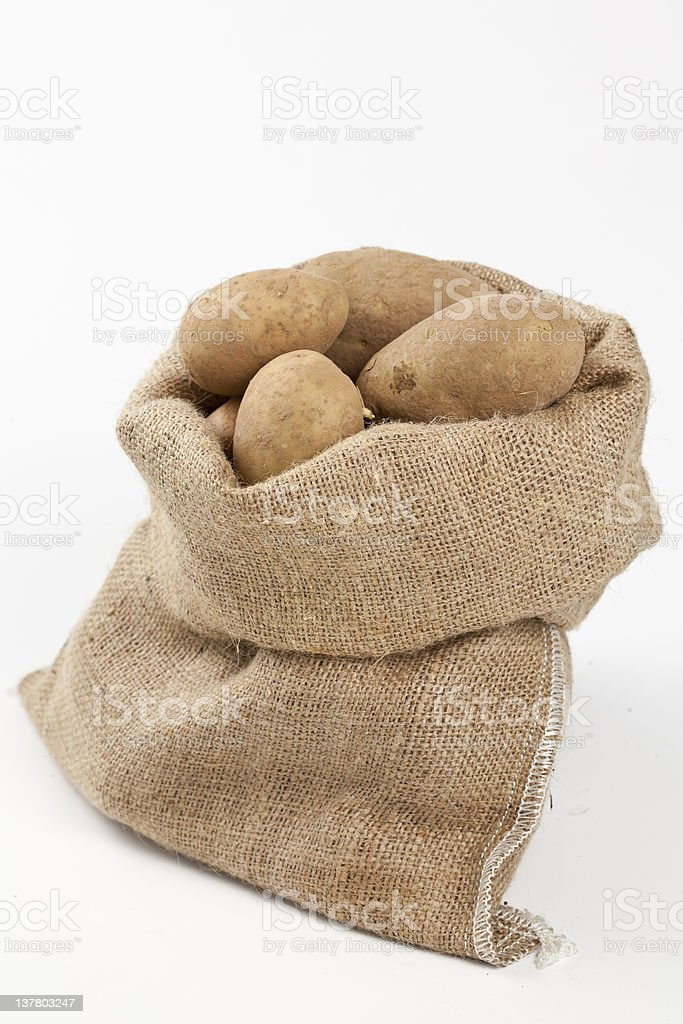 Raw potatoes in burlap bag isolated royalty-free stock photo