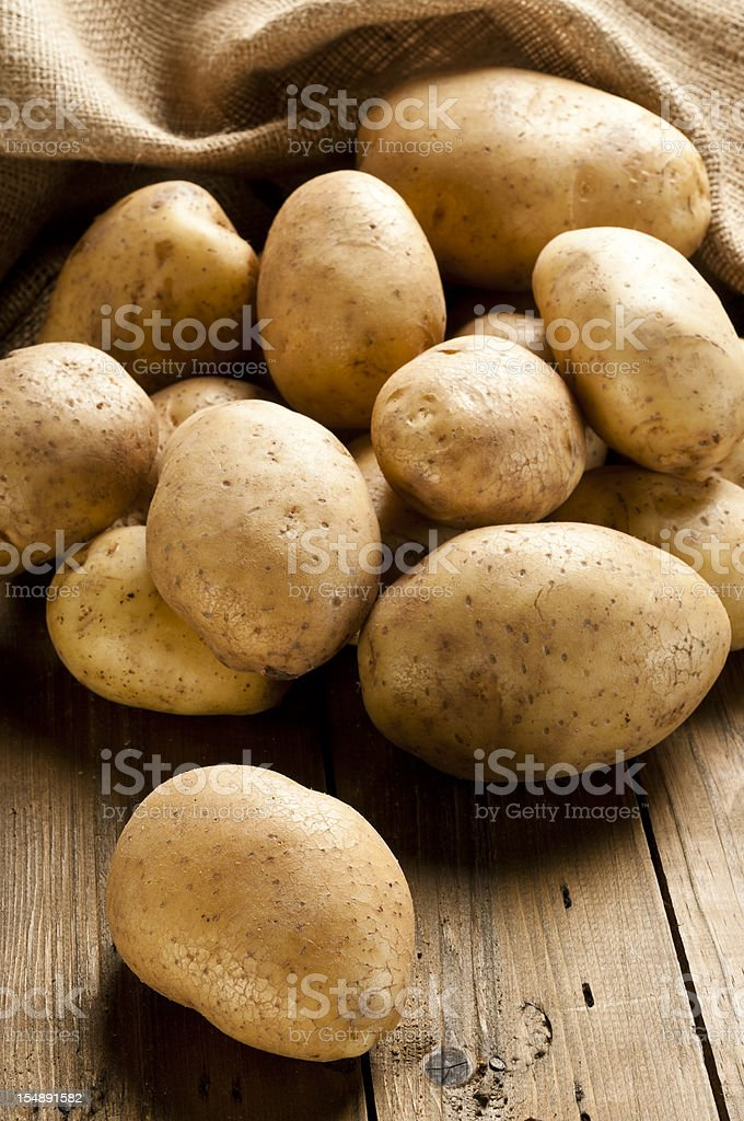 Raw potatoes out of a sack on rustic wood table stock photo