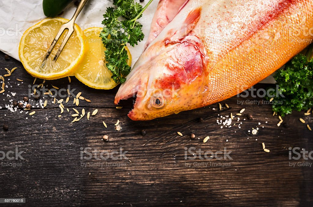 raw rainbow trout fish preparation on old wooden table stock photo