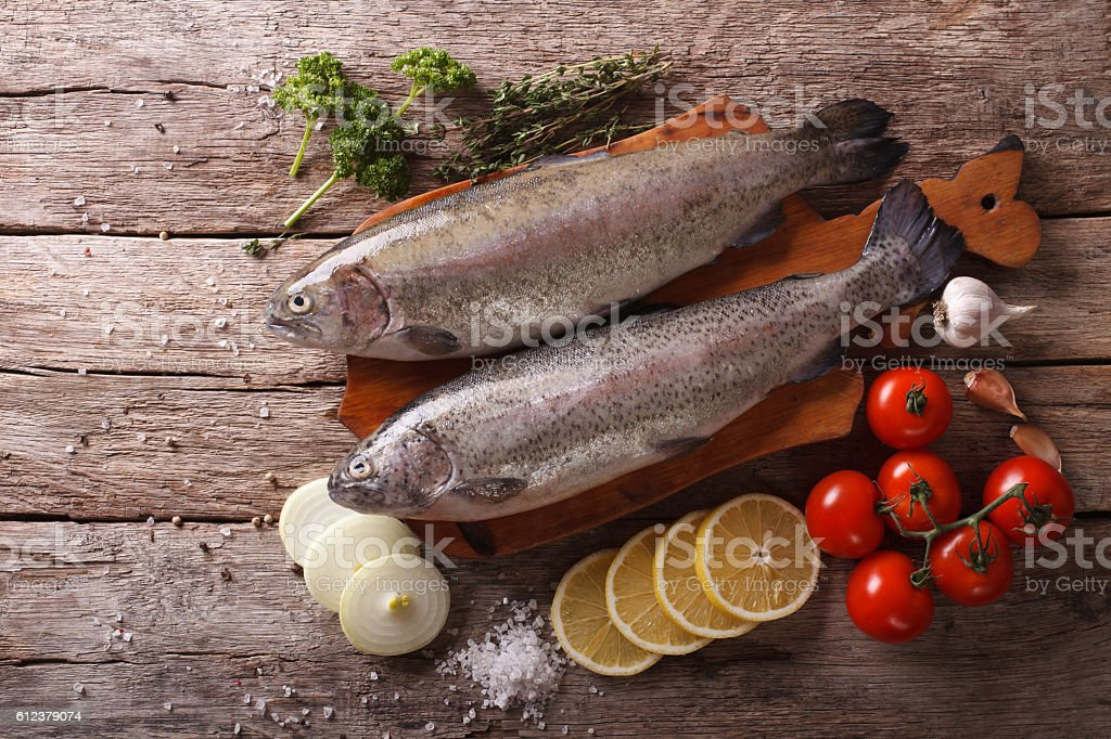 raw rainbow trout with ingredients on a table. Horizontal stock photo