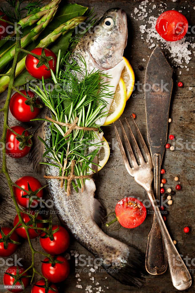 Raw rainbow trout with lemon, herbs and spice stock photo