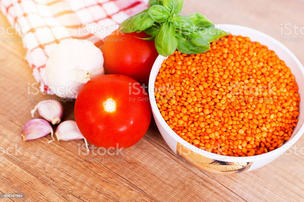 Raw red lintil whit tomatoes, garlic and basil stock photo