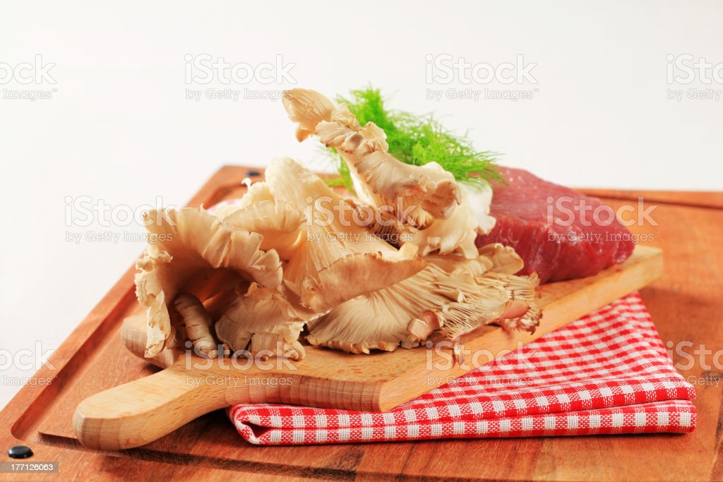 Raw red meat and oyster mushrooms royalty-free stock photo