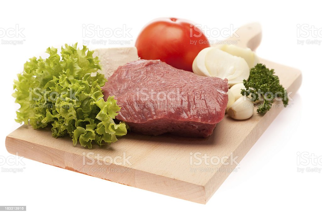 Raw red meat with assorted vegetables on cutting board royalty-free stock photo