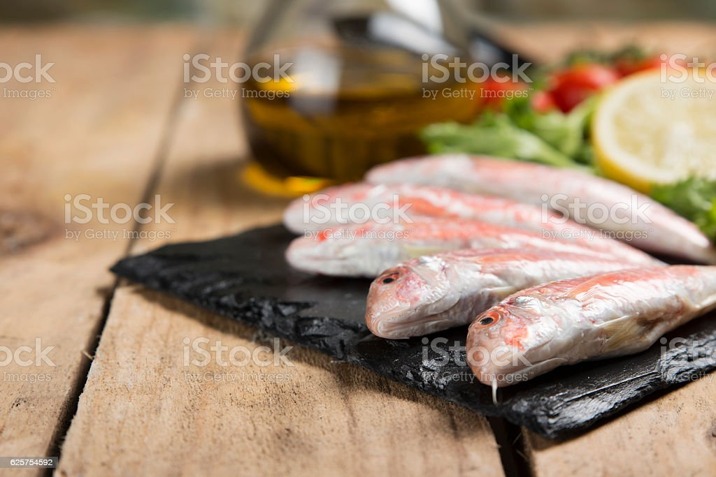 raw red mullet served on curly salad on slate plate stock photo
