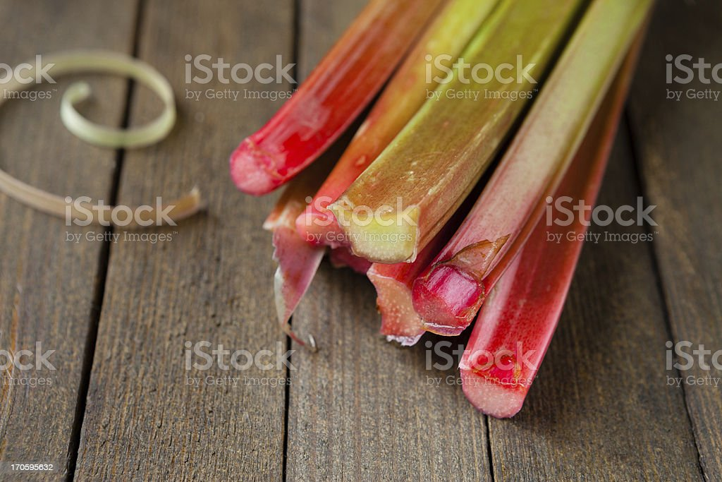 raw rhubarb stalks on a wooden surface stock photo