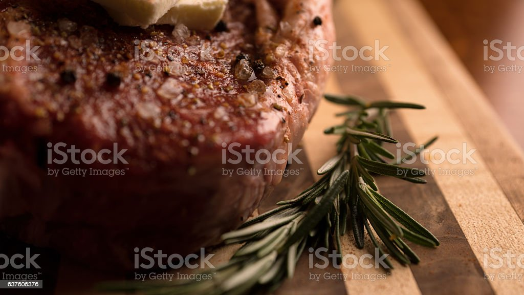 Raw Rib Eye Steak with Butter and Seasonings stock photo