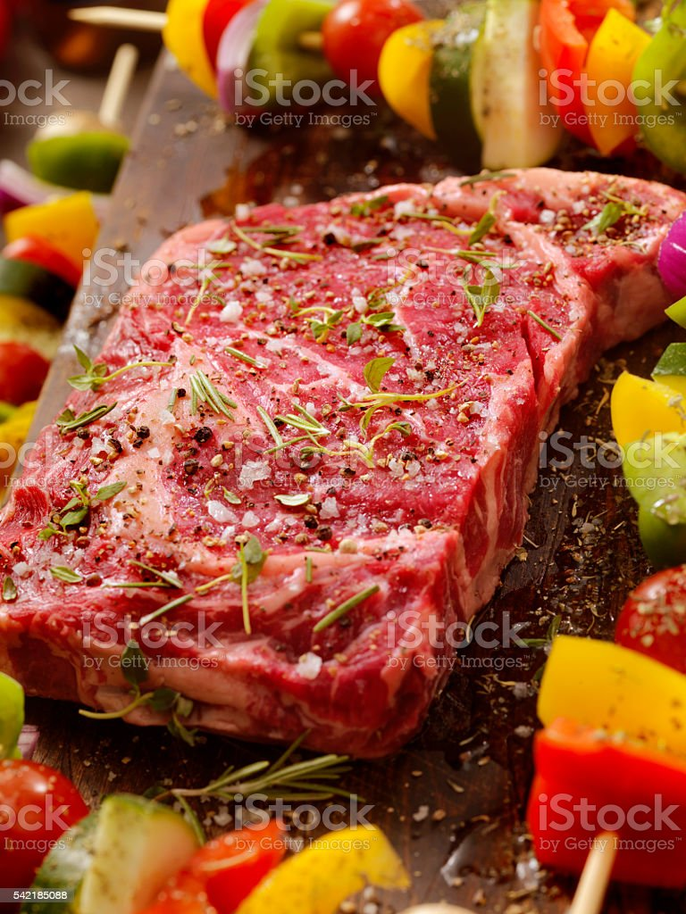 Raw Rib Eye Steak with Vegetable Kabobs stock photo