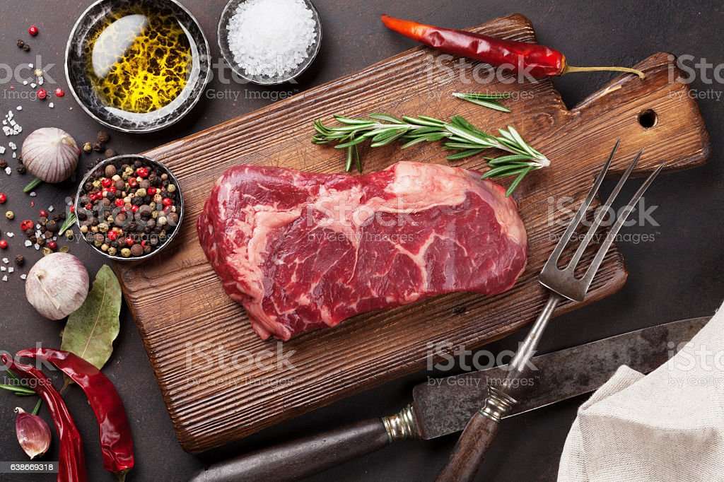 Raw ribeye beef steak cooking with ingredients stock photo