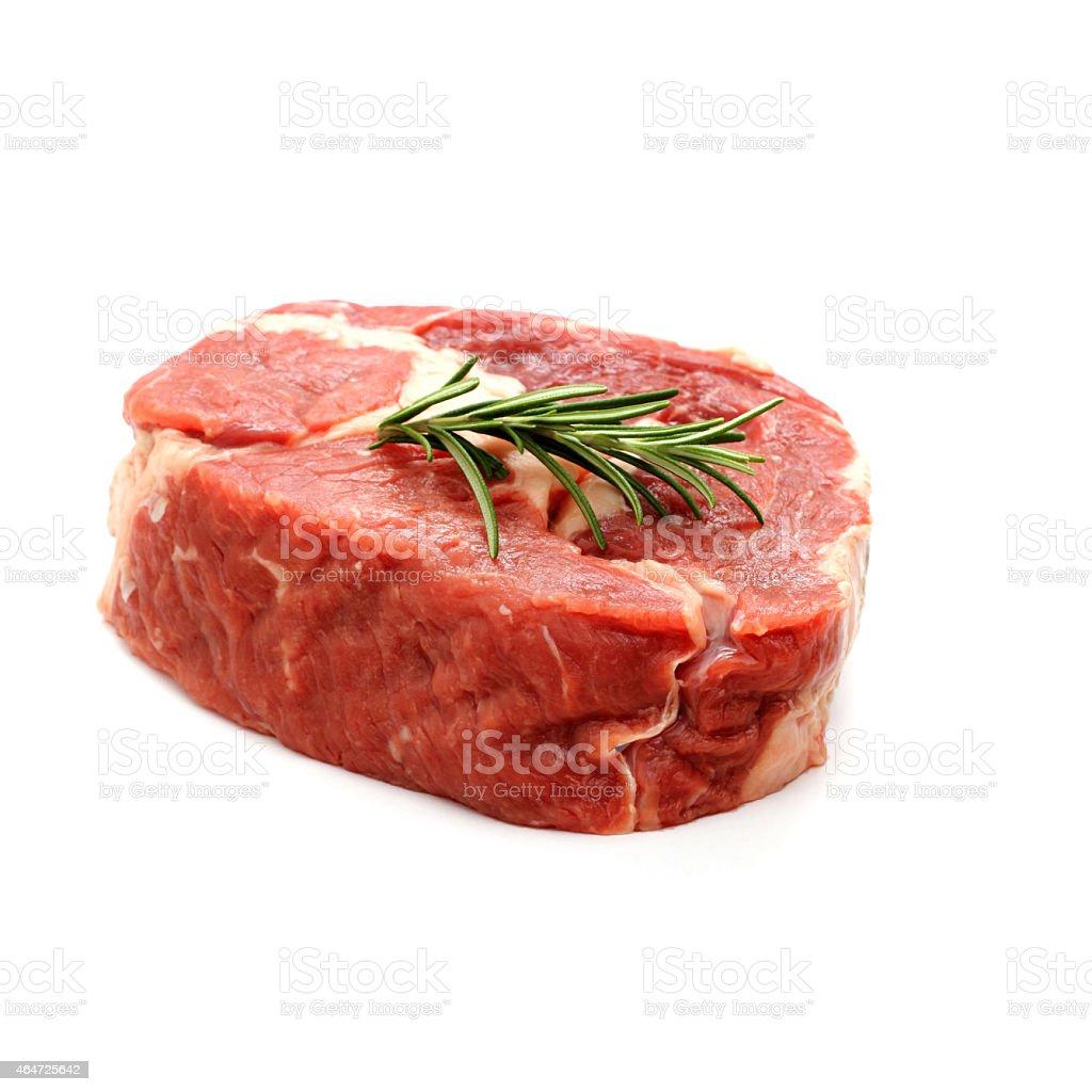 Raw ribeye steak garnished with sprig of rosemary stock photo