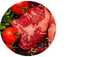Raw Ribeye Steak with fresh herbs, tomatoes, and spices on