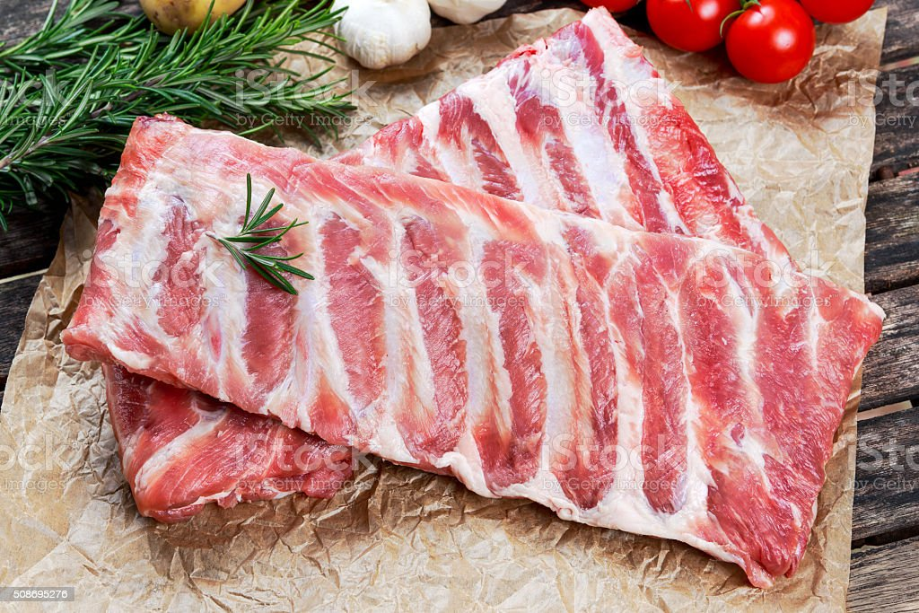 Raw ribs with a rosemary and vegetables. on crumpled paper stock photo