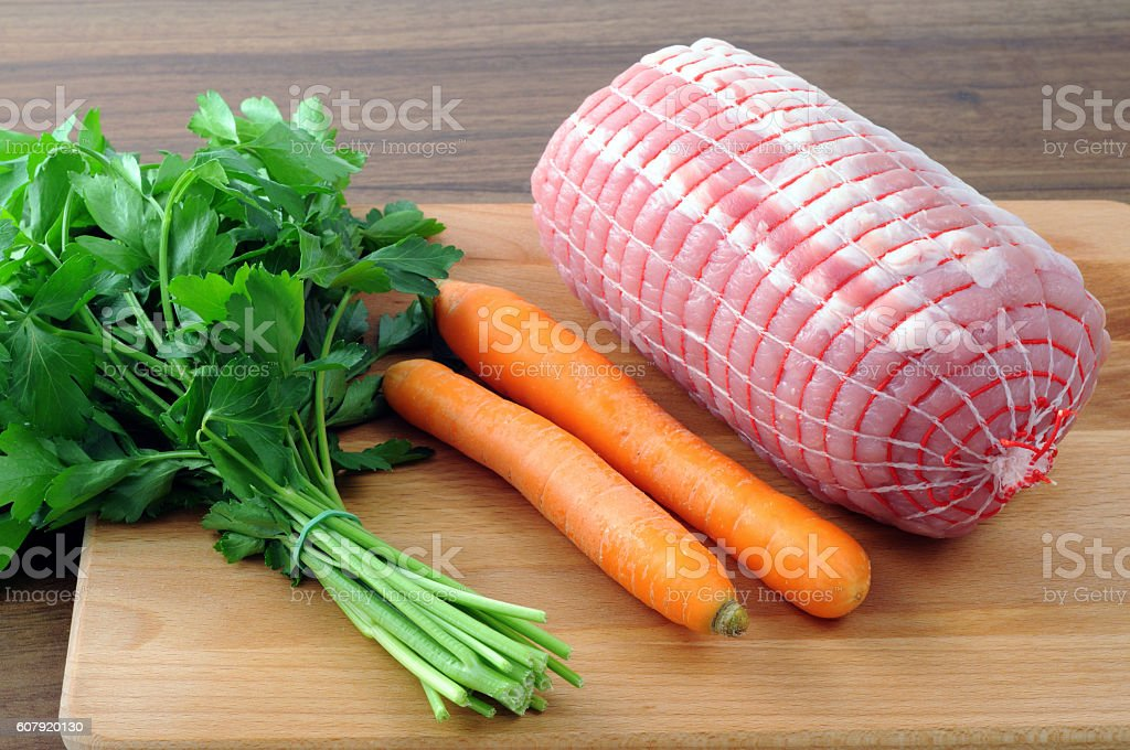 raw rolled pork meat with parsley and carrots. stock photo