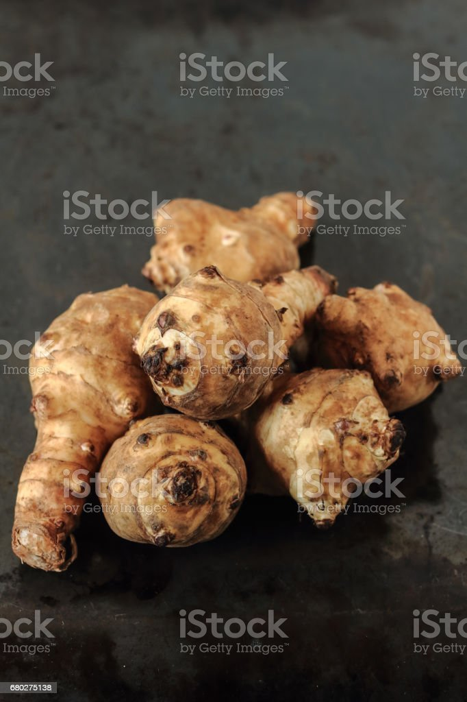 Raw roots of topinambur on dark background stock photo