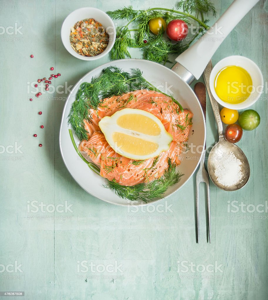 Raw salmon fillet in frying pan and fresh ingredients stock photo