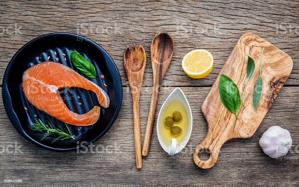 Raw salmon fillet in the black plate with ingredients olive stock photo