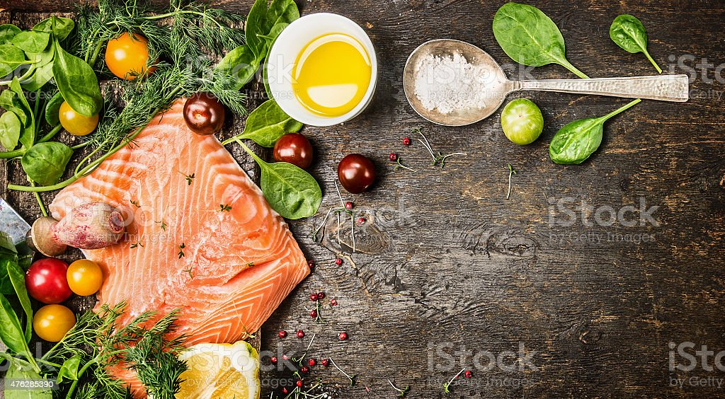 Raw salmon fillet, spoon, herbs and spices on rustic background stock photo
