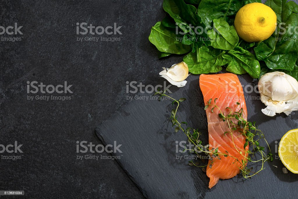 Raw salmon fillet with ingredients on a dark slate plate stock photo