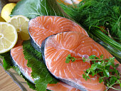 Raw salmon fillets with fresh greens and lemon