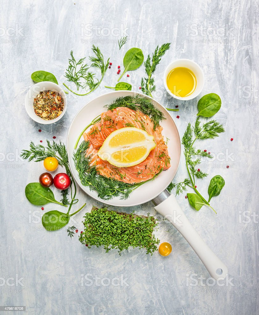 raw salmon in white pan with lemon and fresh herbs stock photo